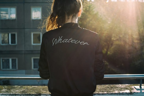 "Woman facing away, wearing a jacket that says ""whatever"" on the back"