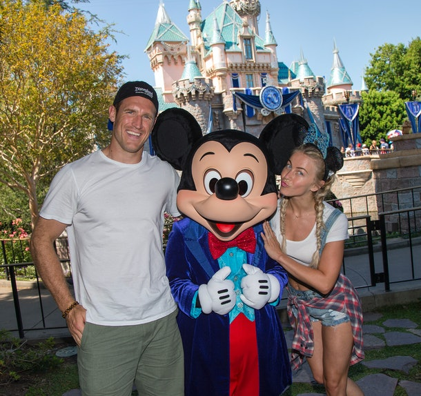Julianne Hough and Brooks Laich posing for a picture in front of the castle with Mickey Mouse is a fun Disneyland activity for couples.