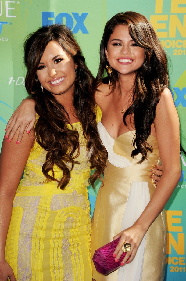 Selena Gomez and Demi Lovato flash wide smiles at the 2011 Teen Choice Awards.