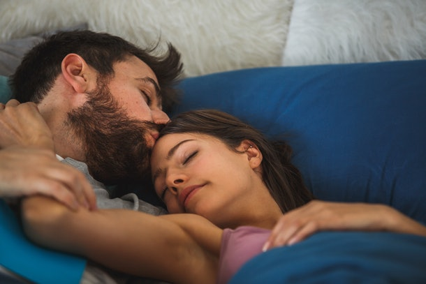 A couple sleeps peacefully in bed, as the man kisses the woman's head.