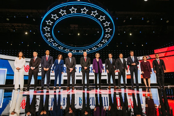 Four women presidential candidates, with eight male candidates, on stage for the debate