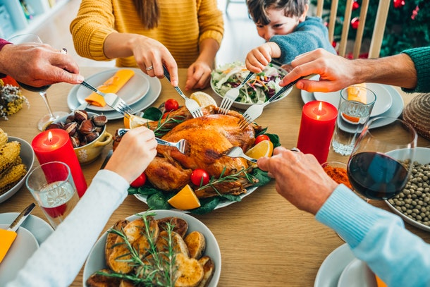 A family surrounds a Thanksgiving dinner table and sticks their forks into the turkey in the middle.