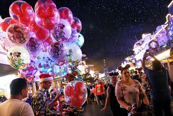 Disney lovers walk down a crowded Main Street during Mickey's Very Merry Christmas Party.