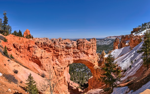 Bryce Canyon National Park in Utah is covered with snow on a sunny day in the middle of winter.