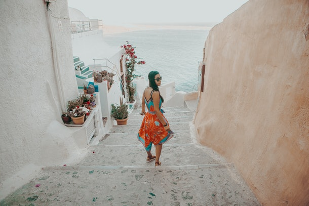 A woman walks down stairs toward the ocean while on an underrated family vacation in Santorini, Greece.