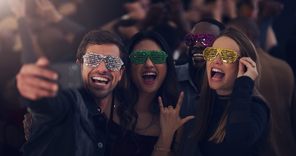 A group of four friends in sparkly sunglasses take a selfie in a club on New Year's Eve.