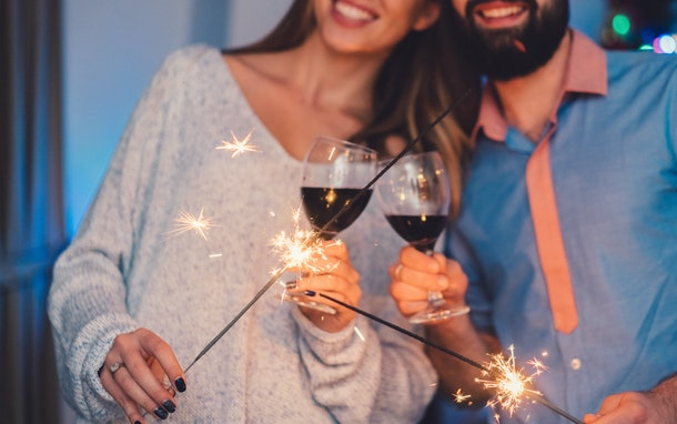 A couple toasts their red wine glasses and hold sparklers on New Year's Eve.