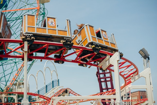The orange cart of a coaster in Coney Island zooms down its red track.