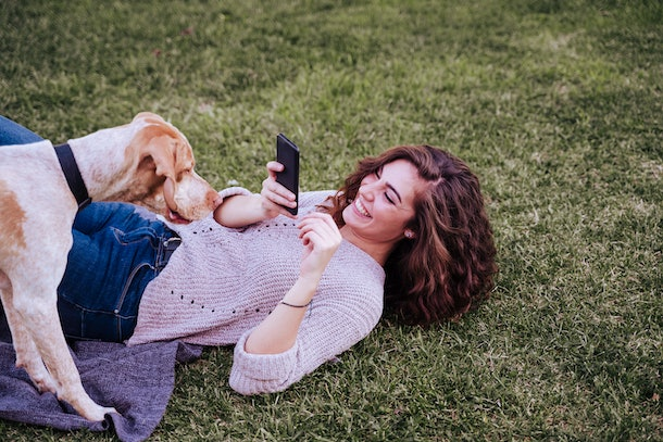 A woman lays in the grass and laughs while taking a picture of her dog on her phone.