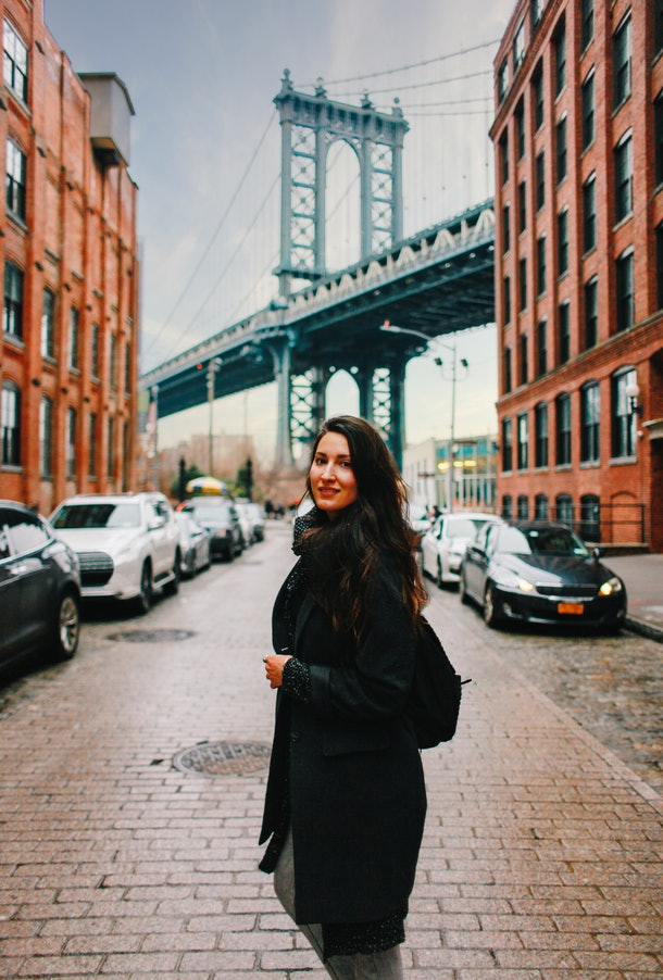 A chic woman poses with the view of the Brooklyn Bridge and warehouses in Dumbo, Brooklyn.