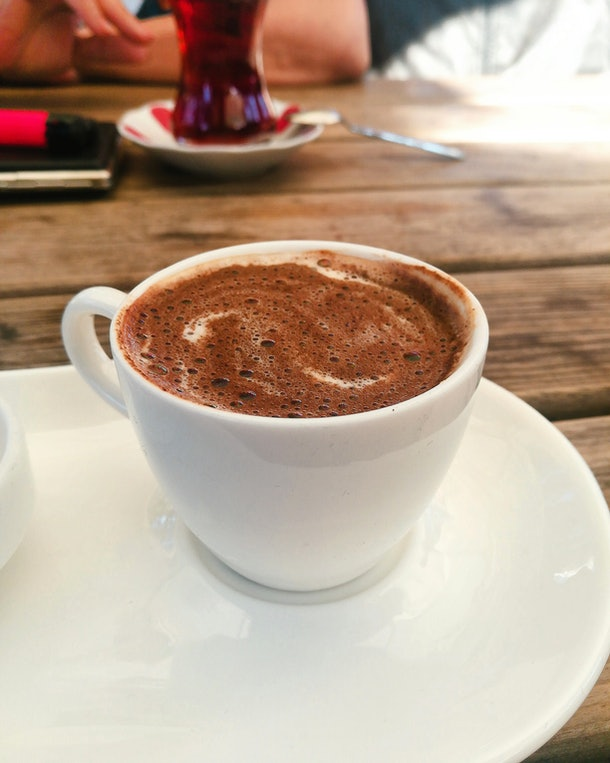 A cup of hot chocolate sits on a wood table.