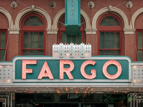 The sign of the Fargo Theatre in Fargo, North Dakota glows in pink and teal.