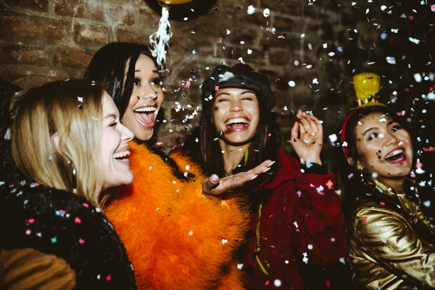 A group of stylish friends laughs and throws confetti in the air while out for New Year's Eve.