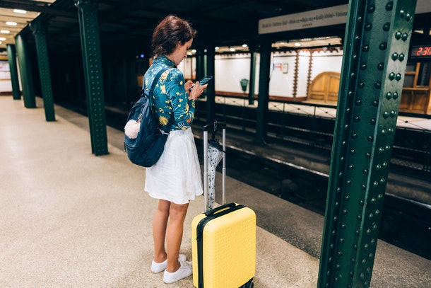 A woman stands in a subway station in a city with a yellow suitcase by her side.