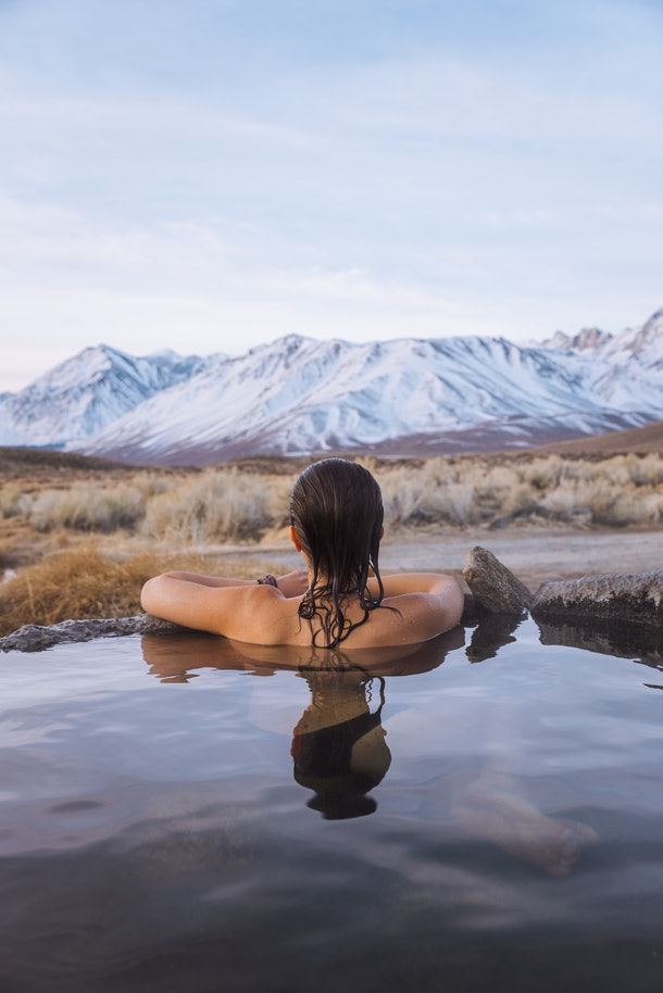 A woman soaks in a hot spring while looking at snowy mountains on an international trip.
