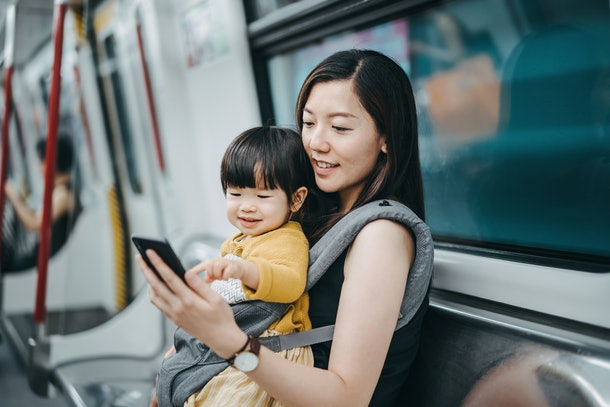 An Asian woman plays on her phone while holding her new nephew and riding the subway.