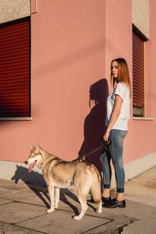 A woman poses against a pink wall in the city with her large dog.