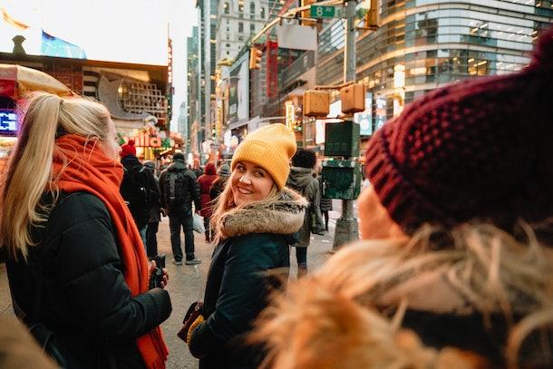 Three friends walk around New York City in the wintertime.