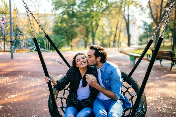 A happy couple sits on a large swing in the park.