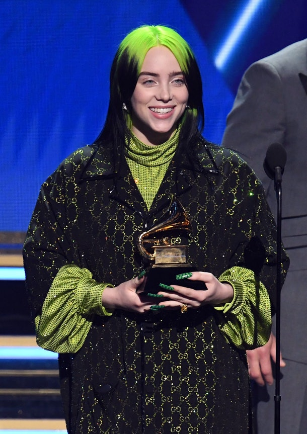 Billie Eilish smiles and holds a Grammy award on stage at the 2020 Grammys.