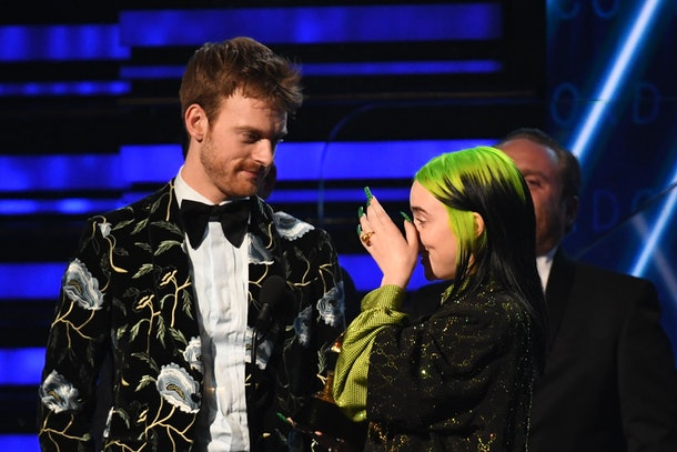 Billie Eilish stands on stage with her brother while accepting a Grammy award.