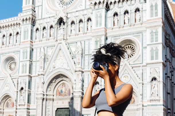 A young woman takes a picture on her digital camera while standing near the Duomo in Florence, Italy.