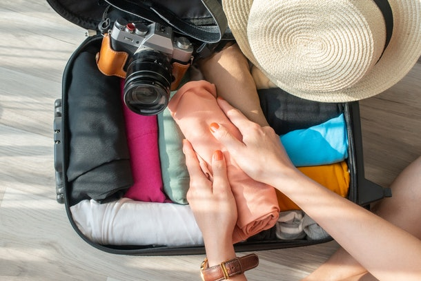 A woman rolls her clothes to better fit them into a carry-on bag before a trip.