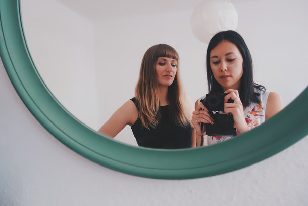Two women pose for a mirror selfie in a mirror on the wall.