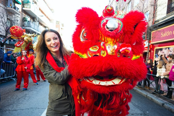 A woman poses with a dragon during a parade for the Lunar New Year.