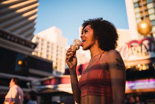 A woman licks an ice cream cone outside of a hotel in Las Vegas, Nevada.