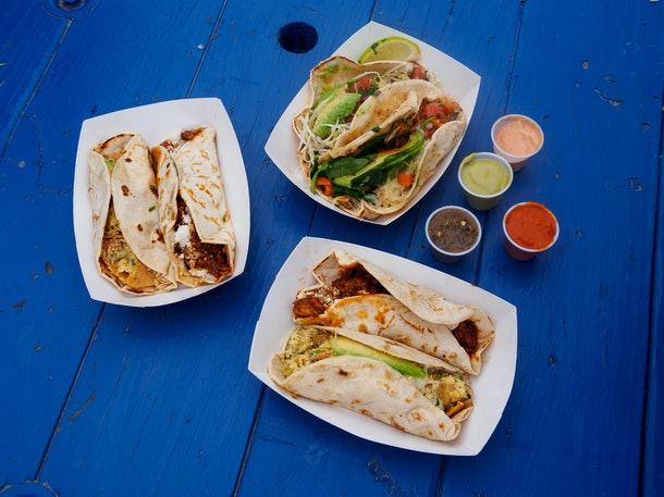 Breakfast tacos sit on a bright blue picnic table in Austin, Texas.