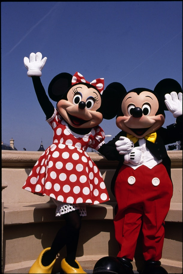 Minnie and Mickey Mouse wave to the camera while posing in Disneyland Paris.