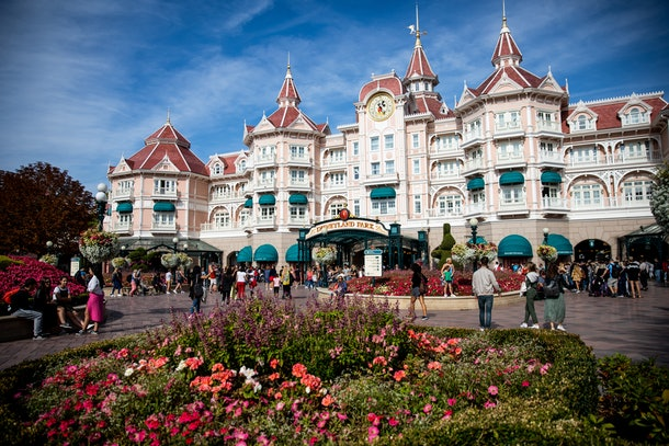 The main entrance to Disneyland Paris is decorated with flowers on a sunny, bustling day.