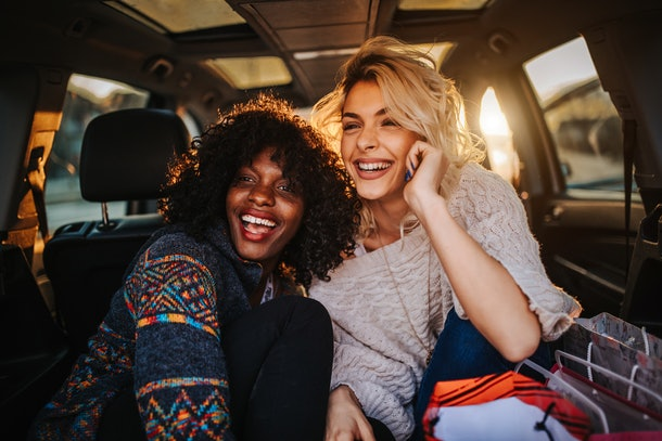 Two young women laugh while sitting in the trunk of a car at golden hour during a fall staycation.