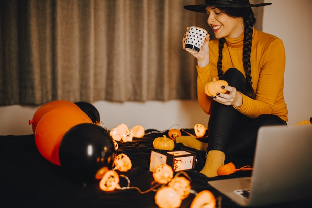 A woman in a witch hat, surrounded by Halloween decorations, holds a cup of coffee.