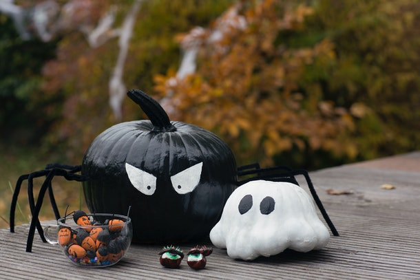 Two painted pumpkins, that have been crafted to look like a spider and ghost, sit on a wooden table outside.