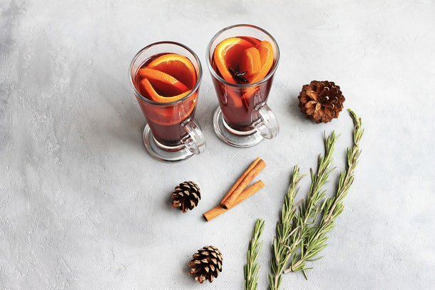 Two fall-inspired cocktails sit on a concrete table with cinnamon sticks and pinecones.
