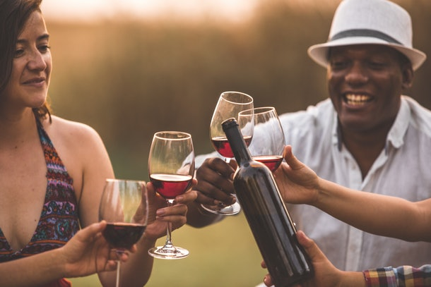 Three people cheers their red wine glasses outside at a vineyard.