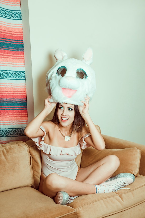 A brunette woman wearing a pink off-the-shoulder dress and white sneakers smiles while she sits on a couch and puts a bunny mask over her head.