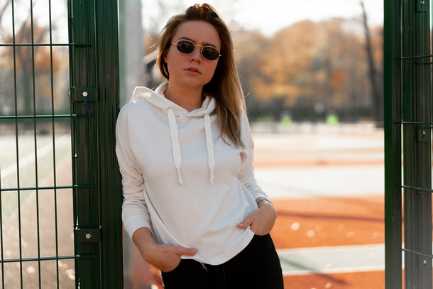 A young stylish woman poses in a white hoodie in front of a basketball court.