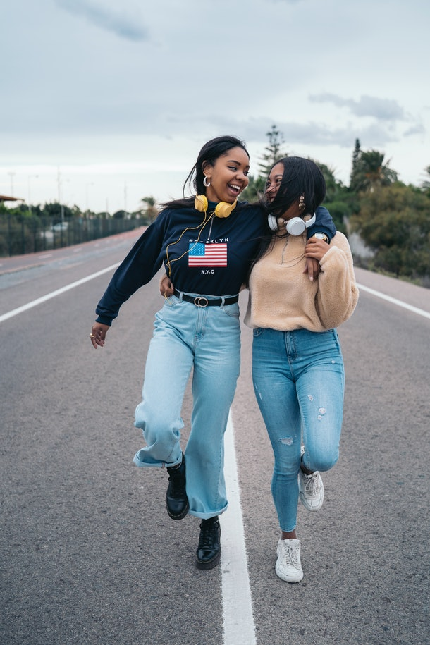 Two young Black women skip on a road while wearing sweatshirts and headphones.