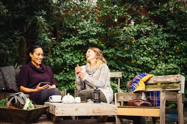 Two young women sit in their backyard and drink tea while wearing sweaters.