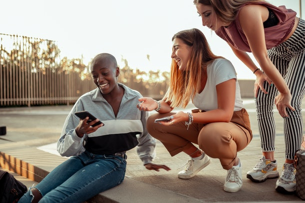 Three friends laugh at something on one their phones.