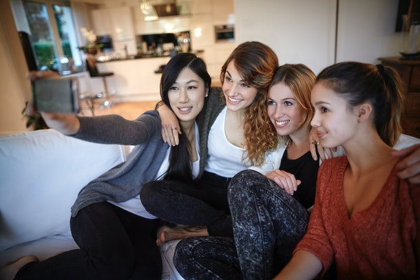 A group of women sitting on the couch at home, pose for a selfie.