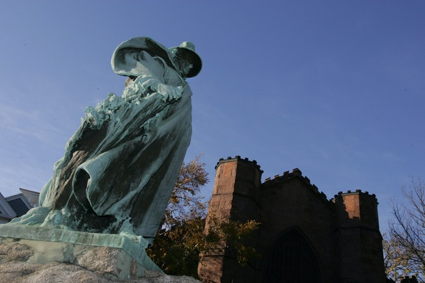 A statue outside of the Salem Witch Museum stands against a bright purple sky.
