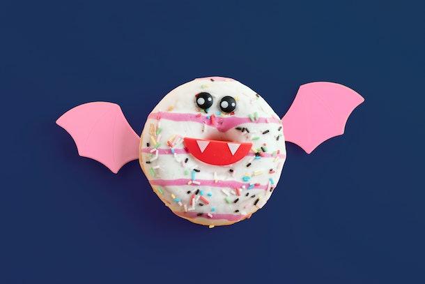 A doughnut decorated like a bat sits on a blue table.