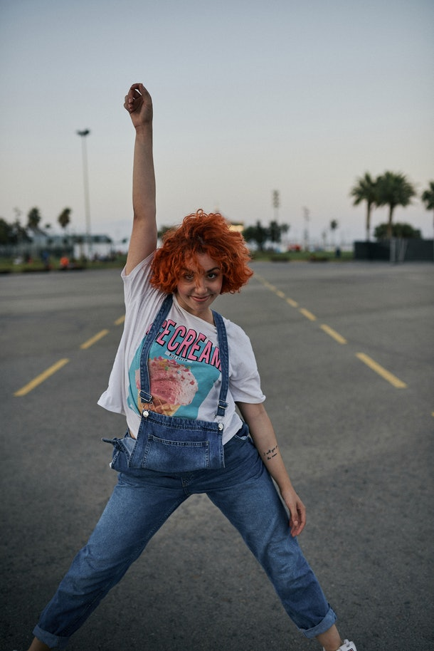 A young Latinx woman with orange hair and spunky style poses in a parking lot with palm trees at dusk.