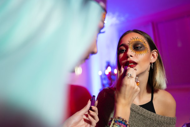 A young woman puts costume makeup on her friend for Halloween.