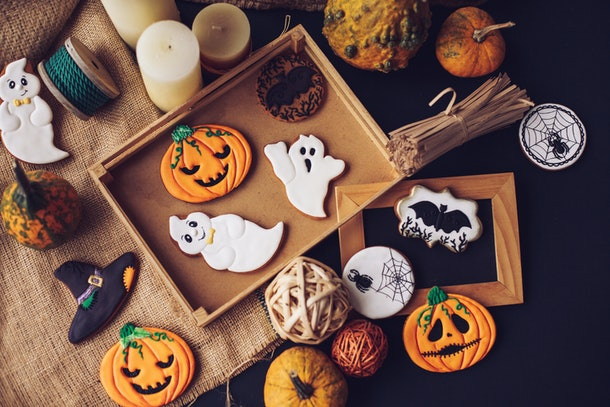 A batch of Halloween cookies, decorated like pumpkins, spiderwebs, and witch's hats, are place on the table.