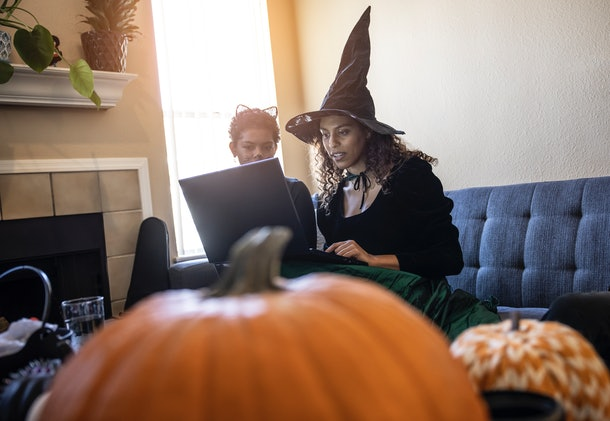 Two young women sit with their laptop on a couch while wearing Halloween costumes and video chatting.